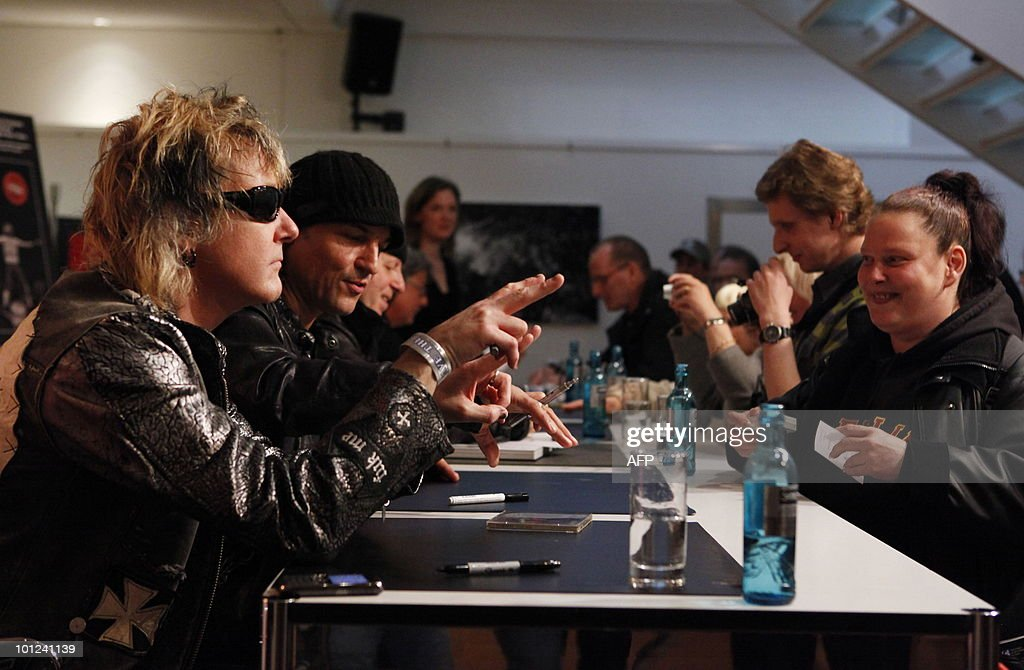 Members of the German rock band Scorpions including James Kottak (L) sign books for fans after a press conference on May 28, 2010 at the Dussmann bookshop in Berlin during the presentation of a new coffee-table book by photographer Marc Theis. The photographer accompanied the band on their world tour from 2007 to 2009.