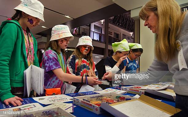 Members of the Girl Scouts of Central Maryland gather around educational circuit boards as they work on technology badges during a shoppingmall...