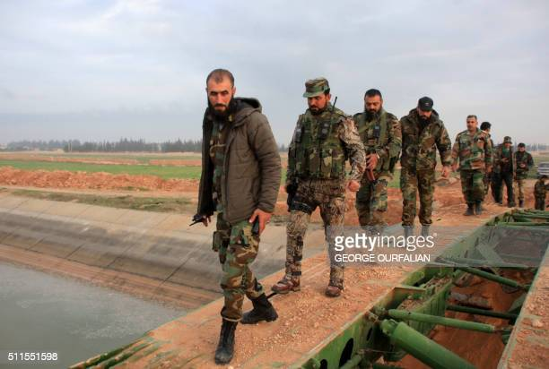 Members of the government forces cross a retractable military bridge on the eastern outskirts of the Syria's northern embattled city of Aleppo after...