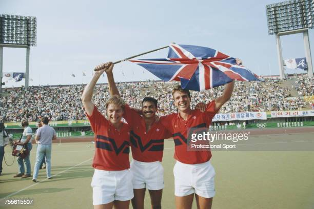 Members of the Great Britain field hockey team celebrate with the United Kingdom union national flag after the Great Britain team beat West Germany...