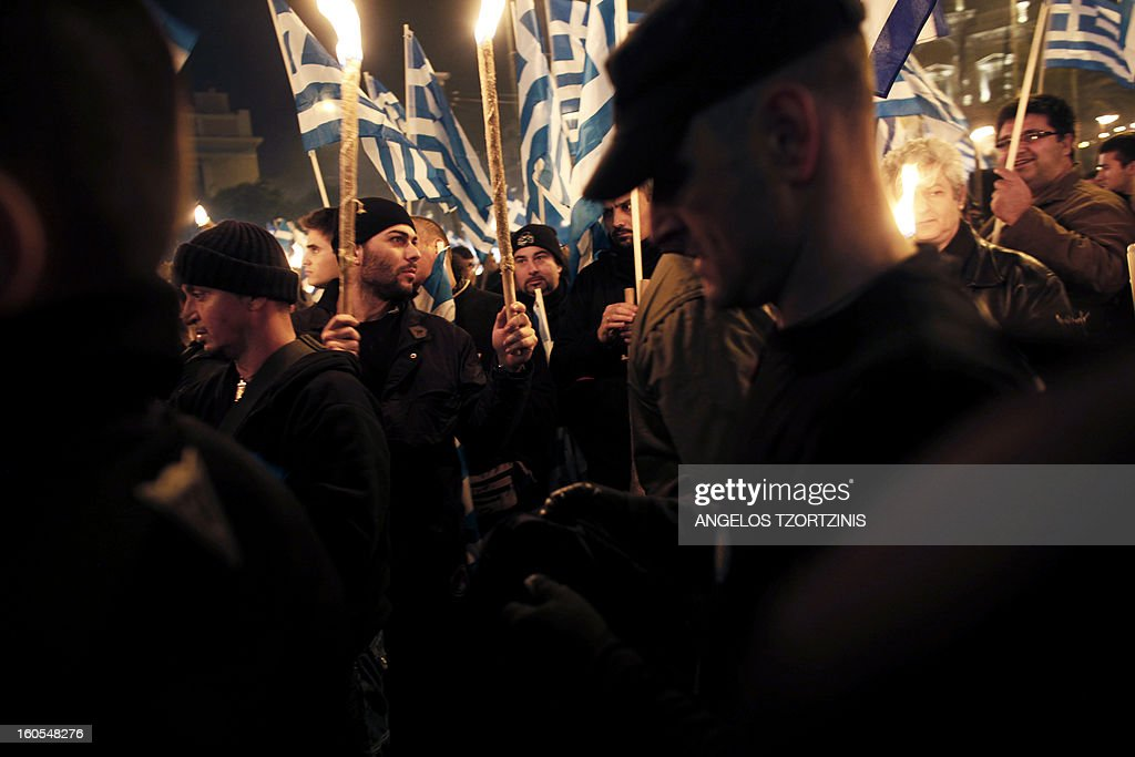 Members of the Greek ultra nationalist Golden Dawn party hold Greek national flags on February 2, 2013 during a gathering of Greek nationalists in central Athens, to commemorate the death of three Greek military officers. The crew of a Greek army helicopter crashed on January 31 at open sea in the Imia islets, at the Greek-Turkish sea borders, during a military crisis and subsequent dispute between the two countries over sovereignty of the islets in 1996. AFP PHOTO ANGELOS TZORTZINIS