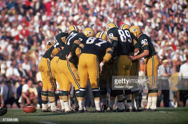 Members of the Green Bay Packers football team huddle together to discuss their next play during Super Bowl I against the Kansas City Chiefs at...