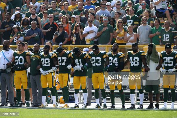 Members of the Green Bay Packers stand with arms locked as a sign of unity during the national anthem prior to their game against the Cincinnati...