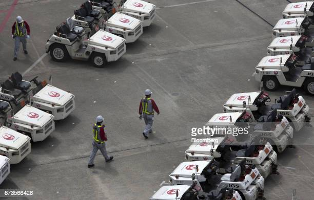 Members of the ground crew for Japan Airlines Co walk between ground transportation vehicles at Haneda Airport in Tokyo Japan on Wednesday April 26...