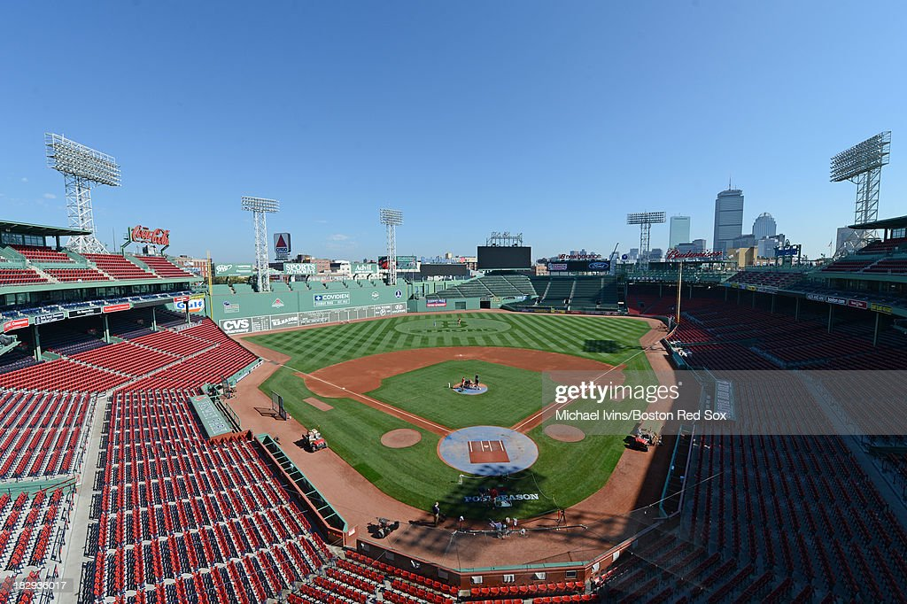 Members of the ground crew paint the post season logo and prepare the field for a team workout on October 2, 2013 at Fenway Park in Boston, Massachusetts.