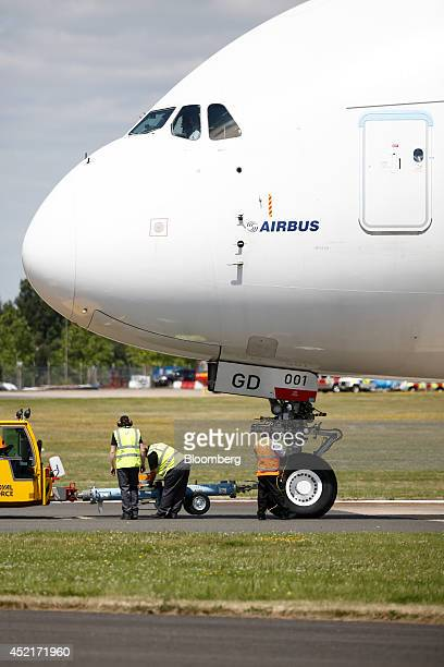 Members of the ground crew work beneath the nose cone of an Airbus A380 aircraft produced by Airbus Group NV as it waits on the tarmac on the first...