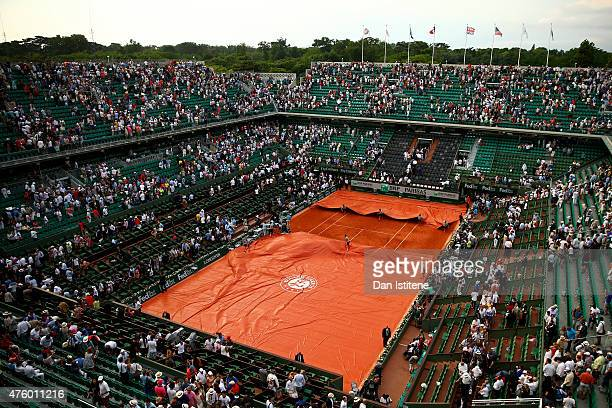 Members of the ground staff pull the rain covers across the court as rain suspends play in the Men's Semi Final match between Andy Murray of Great...