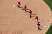 Members of the grounds crew drag the infield during a game between the St Louis Cardinals and the Miami Marlins at Busch Stadium on July 6 2013 in St...
