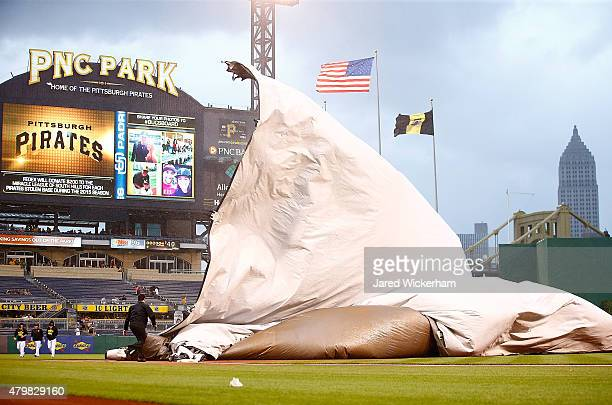 Members of the grounds crew get caught underneath the tarp while heavy wind and rain came down causing a rain delay between the Pittsburgh Pirates...