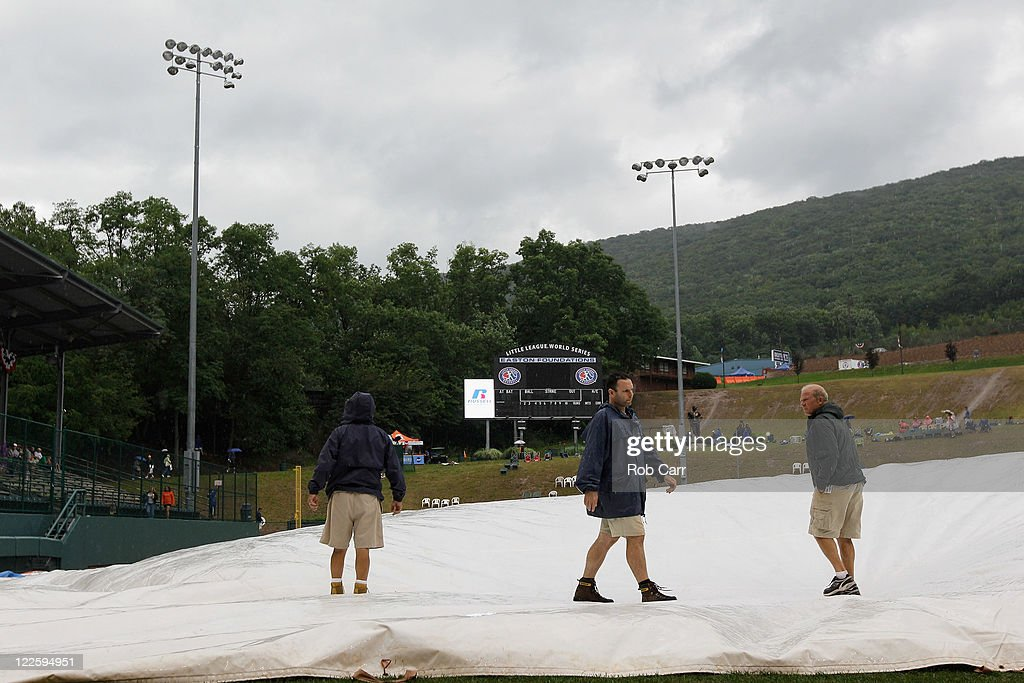 Members of the grounds crew inspect the tarp during a rain delay before the start of the Little League World Series championship game between the Japan team from Hamamatsu City, Japan and the West team from Huntington Beach, California on August 28, 2011 in South Willamsport, Pennsylvania.