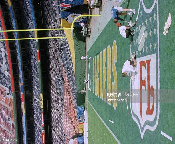 Members of the grounds crew paint logos in the end zone 20 January at Qaulcomm Stadium in San Diego CA in preparation for Super Bowl XXXII The...
