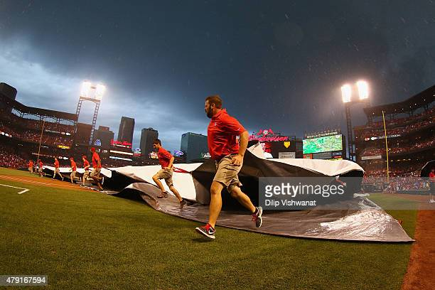 Members of the grounds crew pull the tarp over the field as it begins to rain prior to an interleague game between the St Louis Cardinals and the...