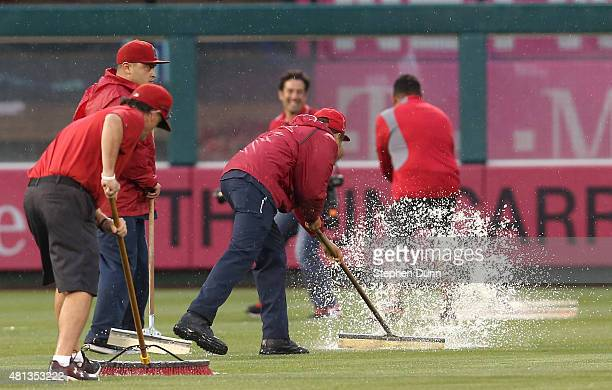 Members of the grounds crew sweep water in the outfield as the game between the Boston Red Sox and the Los Angeles Angels of Anaheim is delayed for...