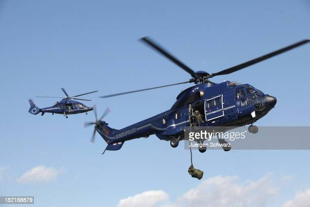 Members of the GSG 9 antiterrorism unit of the German Federal Police use a Eurocopter Superpuma and a Eurocopter EC155 when they demonstrate their...