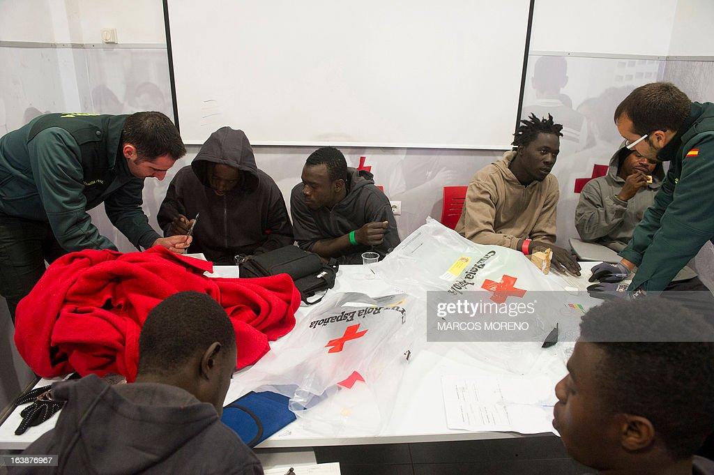 Members of the Guardia Civil try to collect identifications of would-be immigrants, which were rescued off the Spanish coast by the Salvamar Alkaid, at a Spanish Red Cross emergency services local in Tarifa, on March 17, 2013. Spanish rescuers intercepted today a boat carrying 32 sub-Saharan would-be immigrants, 25 men, 6 women and a 8-month-old child, six miles southwest of the port of Tarifa. Some of them suffered from hypothermia.