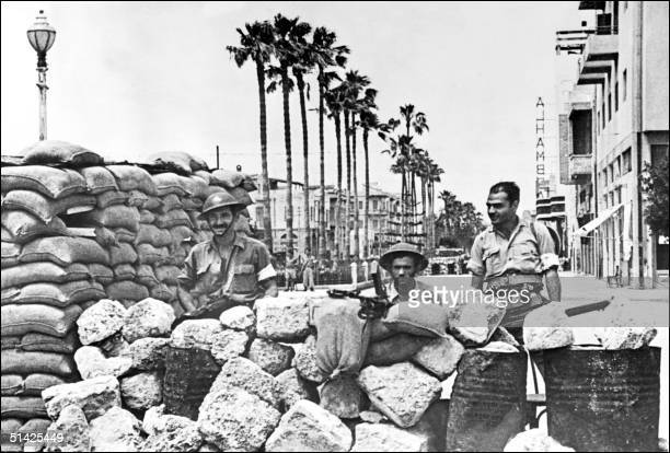 Members of the Haganah the Jewish Agency selfdefense force stand guard behind a barricade 21 May 1948 in Jaffa' streets during fighting with Arab...