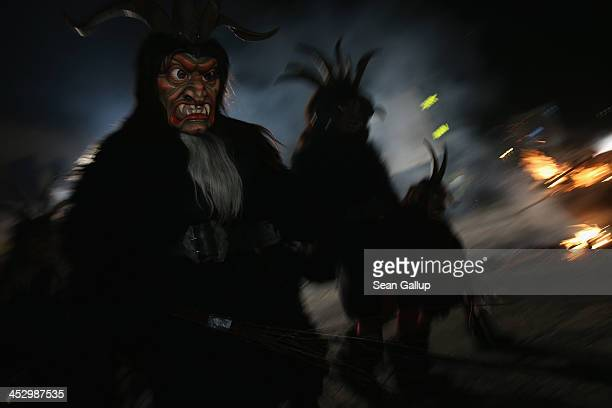 Members of the Haiminger Krampusgruppe dressed as the Krampus creature parade on the town square during their annual Krampus night in Tyrol on...