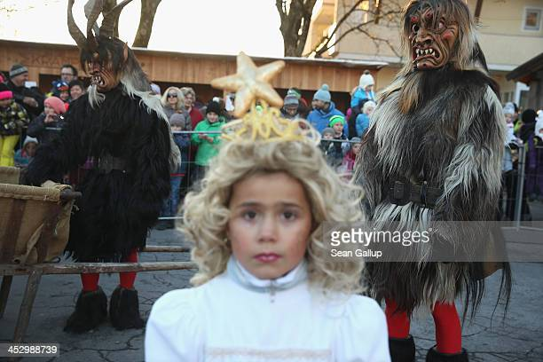 Members of the Haiminger Krampusgruppe dressed as the Krampus creature watch as little girls dressed as angels distribute sweets prior to the annual...