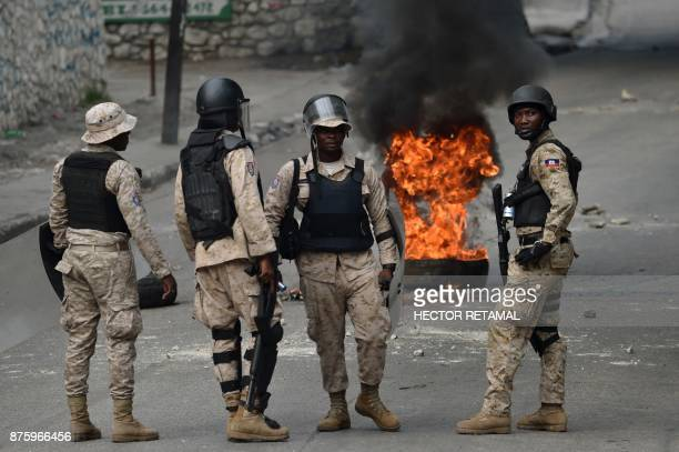 Members of the Haitian police look on during a protest against the remobilisation of the army and angry at a senatorial report that investigated the...