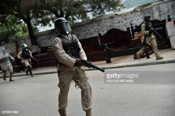 Members of the Haitian police try to break up a protest against the remobilisation of the army and angry at a senatorial report that investigated the...