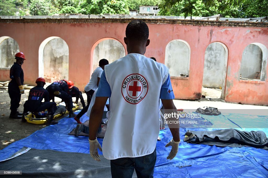 Members of the Haitian Red Cross and Haitian Civil Protection give first aid to people during an Earthquake and Tsunami Emergency drill in the city of Cap-Haitien, on May 6, 2016. The simulation exercise was organised by the Civil Protection Directorate, with the support of the UN Development Programme (UNDP). An estimated 4,500 people participated in the activities during the simulacre. / AFP / HECTOR