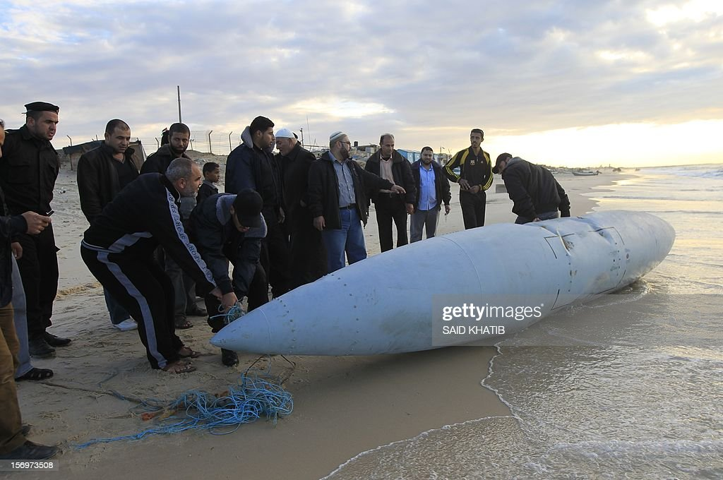 Members of the Hamas-run security forces inspect what appears to be part of an aircraft which washed ashore near Rafah in the southern Gaza Strip on November 26, 2012. Hamas media outlets claimed it was part of an Israeli plane brought down by militants, but there were no identifying marks on the wreckage which could corroborate the allegation that it was part of an Israeli craft.