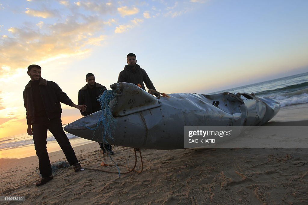 CAPTION - Members of the Hamas-run security forces inspect what appears to be part of an aircraft which washed ashore near Rafah in the southern Gaza Strip on November 26, 2012. Hamas media outlets claimed it was part of an Israeli plane brought down by militants, but there were no identifying marks on the wreckage which could corroborate the allegation that it was part of an Israeli craft. AFP PHOTO / SAID KHATIB