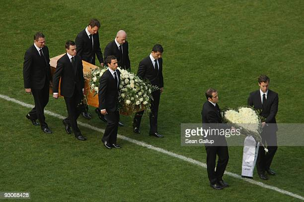 Members of the Hannover 96 football club carry the coffin of their goalie Robert Enke at a memorial service prior to Enke's funeral at AWD Arena on...