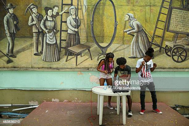Members of the hip hop group Nuevo Mundo use a laptop computer to play American dance music in front of a mural depicting a scene from a Berthold...