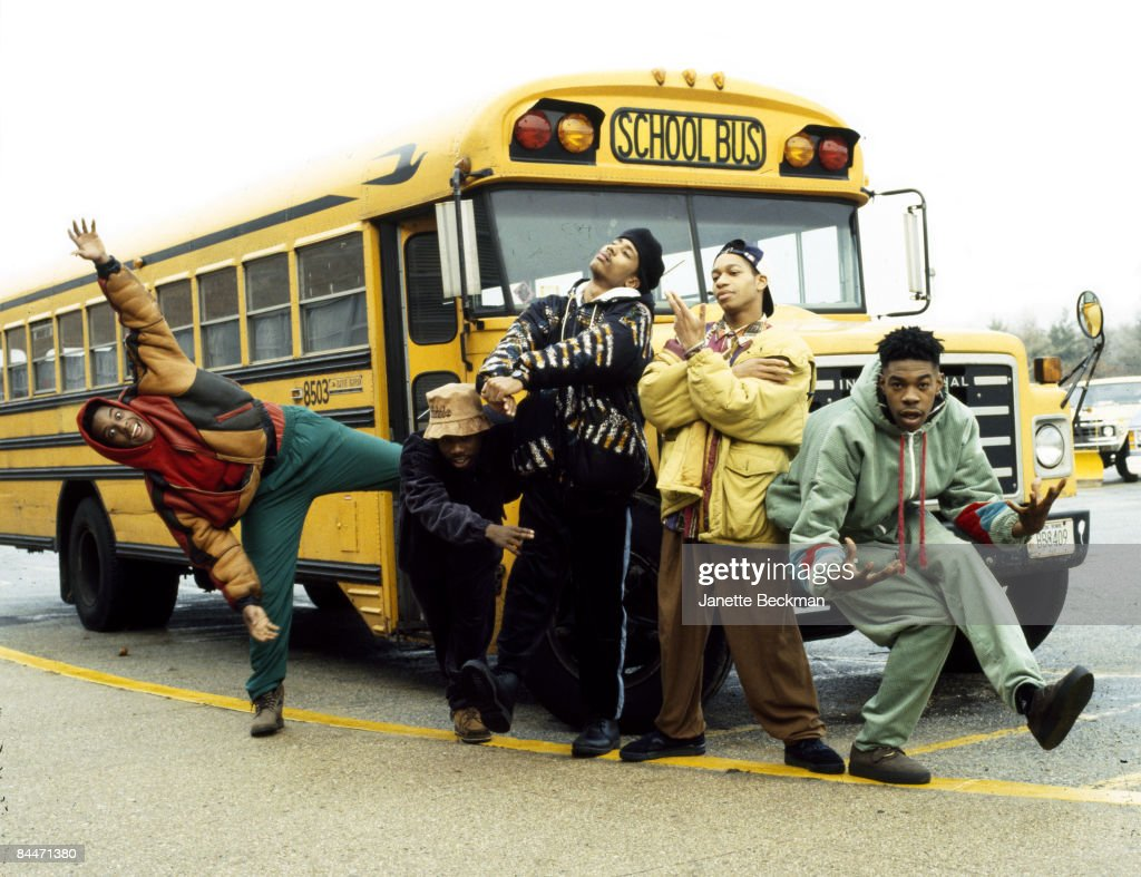 Members of the hiphop group 'Leaders of the New School' pose in front of a school bus, New York, 1991.