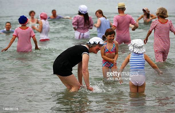 Members of the 'Historische Badegesellschaft' wear historic costumes as they enjoy a bath at the Baltic Sea beach of Heiligendamm northeastern...