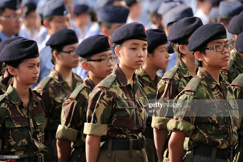Members of the Hong Kong Adventure Corps (HKAC) stand to attention during a flag-raising ceremony at Golden Bauhinia Square in Hong Kong on July 1, 2013 to celebrate the 16th anniversary of the establishment of the Hong Kong Special Administrative Region (HKSAR). Hundreds of thousands of protesters, some waving British colonial-era flags and some sporting Edward Snowden masks, are to march in Hong Kong to denounce the city's leaders and demand universal suffrage on the handover anniversary. AFP PHOTO / ANTHONY WALLACE