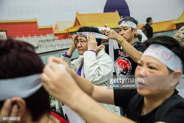 Members of the Hong Kong Alliance in Support of Patriotic Democratic Movements in China tie white bandanas on their foreheads during a protest...