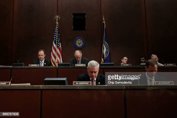 Members of the House Intelligence Committee bow their heads in Christian prayer at the opening of a hearing in the US Capitol Visitors Center June 21...