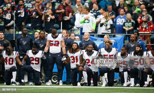 Members of the Houston Texans stand and kneel before the game against the Seattle Seahawks at CenturyLink Field on October 29 2017 in Seattle...