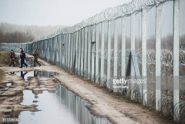 Members of the Hungarian military and Hungarian police force patrol by the razor wired topped security fence on the HungarianSerbian border near...