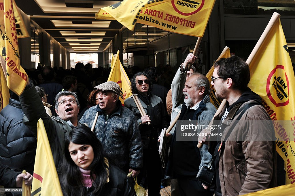 Members of the 'I won't pay' movement protest outside the Public Power Corparation in Athens on March 5, 2013, against the property tax included in the electricity bills. Protesters demanded that the electricity would not be cut off to those who cannot afford to pay the controversial property tax that has been included in utility bills.
