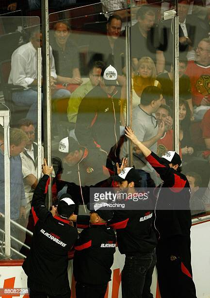 Members of the ice crew replace a pane of glass along the boards during Game Four of the Western Conference Championship Round of the 2009 Stanley...