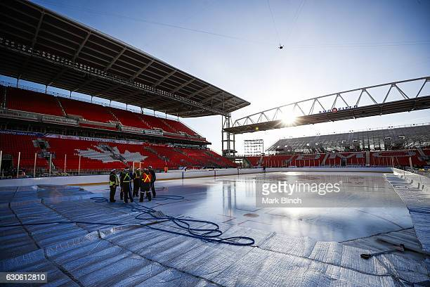Members of the ice crew stand on the ice during the build out of the outdoor rink for the 2017 Scotiabank NHL Centennial Classic between the Detroit...