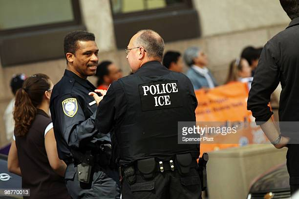Members of the Immigration and Customs Enforcement agency keep watch over demonstrators protesting against a new Arizona law on April 30 2010 outside...