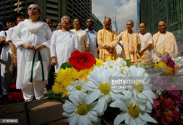 Members of the Indian sect Hare Krishna and the spiritual group Brahma Kumaris offer prayers incense and flowers for victims of tsunamis that hit...