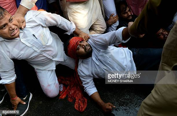 Members of the Indian Youth Congress scuffle with police as they try to detain him during a protest against the demonetisation in New Delhi on...