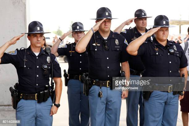 Members of the Indiana State Police salute the flag during the National Anthem prior to the start of the NASCAR Monster Energy Cup Series Brantley...