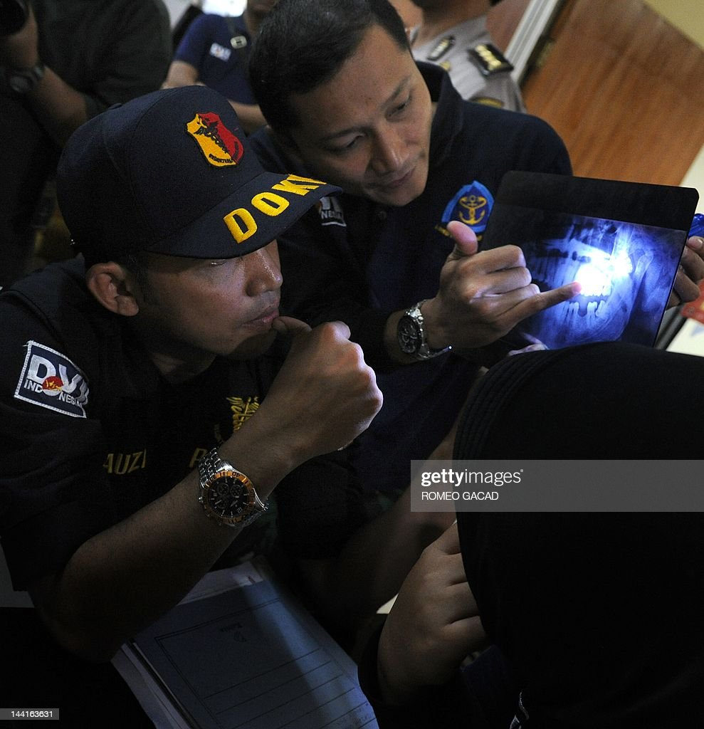 Members of the Indonesian police forensic unit examine dental xrays collected from relatives of missing passengers of the illfated Russian Sukhoi...
