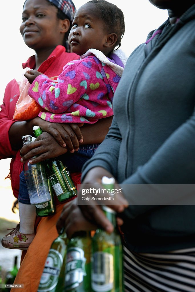 Members of the Indumiso Yamakholwa In Zion church hold used bottles containing blessed water and a written prayer during a ceremony in the Yeoville neighborhood June 21, 2013 in Johannesburg, South Africa. After being prayed over and blessed, worshipers will smash the bottles to release the prayers to God. The worn, arid space on top of the Yeoville hill offers worshipers of various Christian denominations from South African, Botswana, Zimbabwe, the Democratic Republic of Congo and other African nations an open-air space where they can publicly practice their faith with a scenic view of downtown Johannesburg.