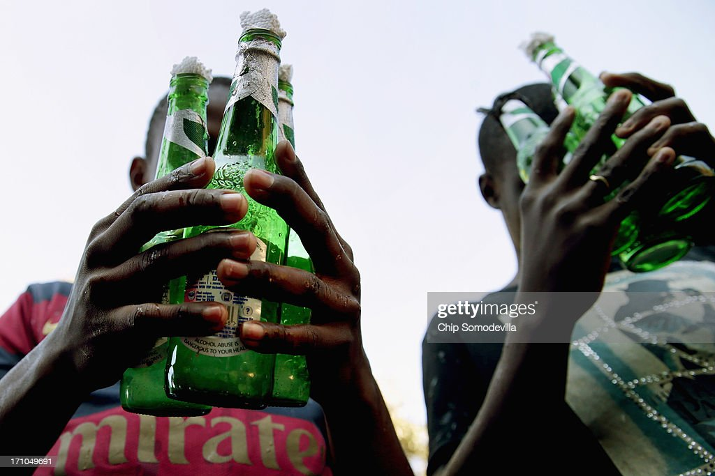 Members of the Indumiso Yamakholwa In Zion church pray while holding used bottles containing blessed water and a written prayer during a ceremony in the Yeoville neighborhood June 21, 2013 in Johannesburg, South Africa. After being prayed over and blessed, worshipers will smash the bottles to release the prayers to God. The worn, arid space on top of the Yeoville hill offers worshipers of various Christian denominations from South African, Botswana, Zimbabwe, the Democratic Republic of Congo and other African nations an open-air space where they can publicly practice their faith with a scenic view of downtown Johannesburg.