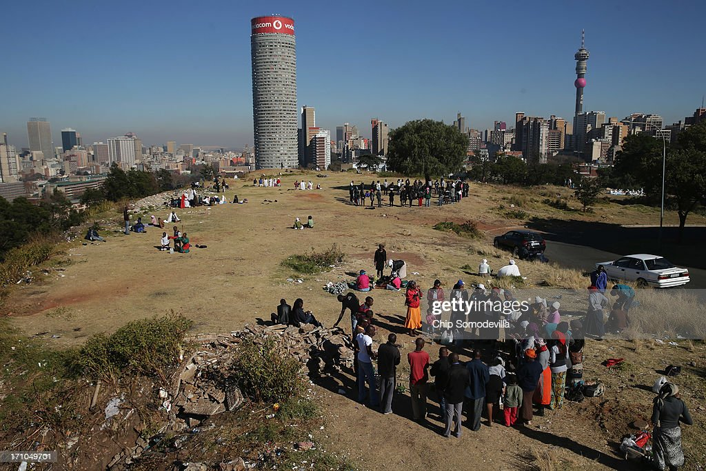 Members of the Indumiso Yamakholwa In Zion church stand in a circle during a prayer service in the Yeoville neighborhood June 21, 2013 in Johannesburg, South Africa. The worn, arid space on top of the Yeoville hill offers worshipers of various Christian denominations from South African, Botswana, Zimbabwe, the Democratic Republic of Congo and other African nations an open-air space where they can publicly practice their faith with a scenic view of downtown Johannesburg.