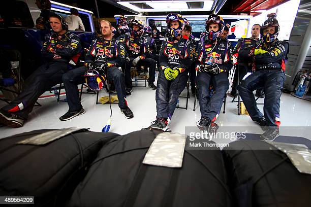 Members of the Infiniti Red Bull Racing pit crew watch the action on the screens in the garage during the Spanish Formula One Grand Prix at Circuit...