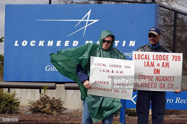 Members of the International Association of Machinists Local 709 carry signs as they walk the picket line outside the Lockheed Martin plant March 8...