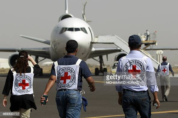 Members of the International Committee of the Red Cross walk towards a plane loaded with Emergency medical aid after it landed at the international...
